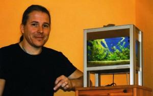 Bild: Aquariendekoration aus Kunststoff / Erik Maik Arnold, der kreative Kopf von Arnold Design Aquarien. Neben ihm steht sein Design Aquarium Foxtrott - Haus am See. Bepflanzt mit Aquariumpflanzen von Tropica.